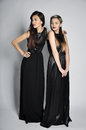 Two beautiful women in a black dresses studio portrait Royalty Free Stock Photos
