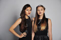 Two beautiful women in a black dresses studio portrait Royalty Free Stock Image
