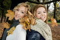 Two beautiful women with dry leaves in the teeth by autumn caucasian Stock Photography