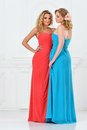 Two beautiful women in evening dresses long studio with white interior Royalty Free Stock Photography