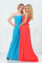 Two beautiful women in evening dresses long studio with white interior Royalty Free Stock Images