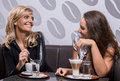 Two beautiful women laughing over a coffee Royalty Free Stock Photo