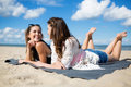 Two beautiful women lying on beach talking and laughing Royalty Free Stock Photo