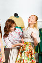 Two beautiful women measuring size of skirt Royalty Free Stock Photo