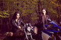 Two beautiful women passionate about motorcycles posing in nature Royalty Free Stock Photos