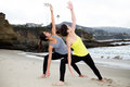 Two beautiful women practicing yoga at beach together Stock Image
