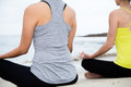 Two beautiful women practicing yoga at beach together Stock Photo