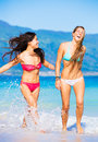 Two beautiful young girls on the beach attractive in bikinis walking and having fun best friends summer lifestyle Stock Photo