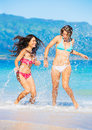Two beautiful young girls on the beach attractive in bikinis walking and having fun best friends summer lifestyle Stock Photos