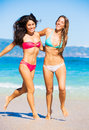 Two beautiful young girls on the beach attractive in bikinis walking and having fun best friends summer lifestyle Royalty Free Stock Photos