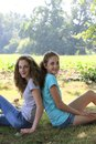 Two beautiful young girls in the park relaxing sitting back to back on ground looking at camera with friendly smiles Royalty Free Stock Photos