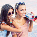 Two beautiful young girls in sunglasses portrait of one holding a skateboard Stock Photography