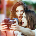 Two beautiful young happy girls make self photo on a professional camera Stock Photography