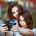 Two beautiful young happy girls make self photo on a professional camera Royalty Free Stock Images