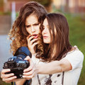 Two beautiful young happy girls make self photo on a professional camera Royalty Free Stock Image