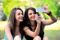 Two beautiful young woman browsing on smart phone in a park Royalty Free Stock Image