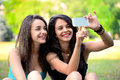 Two beautiful young woman browsing on smart phone in a park Stock Photography