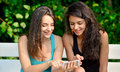 Two beautiful young woman browsing on smart phone in a park while sitting a white bench Royalty Free Stock Image