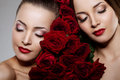 Two beautiful young women with amazing make-up in roses. Cosmetic care, makeup. Sensuality twins. Stylish attractive woman in flo Royalty Free Stock Photo