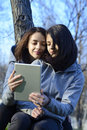 Two beautiful young women browsing a tablet outside while sitting on tree Royalty Free Stock Image