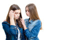 Two beautiful young women comforting one another on white background in jeans jackets Royalty Free Stock Photo
