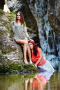 Two beautiful young women leaning on rocks beside a river portrait of Stock Image