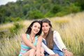 Two beautiful young women sitting on dry grass and smiling Royalty Free Stock Images
