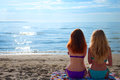 Two beautiful young women sitting on a towel on a beach enjoing the summer Royalty Free Stock Photos