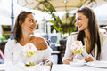 Two beautiful young women smiling and having a fruit salad in a Royalty Free Stock Photo
