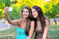 Two beautiful young women taking photo their in park Royalty Free Stock Photo