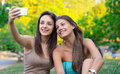 Two beautiful young women taking photo their in park Royalty Free Stock Photos