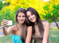 Two beautiful young women taking photo their in park Stock Image