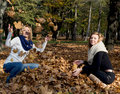 Two beautiful young women throwing yellow leaves in the autumn park Royalty Free Stock Photo