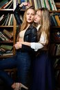 Two beautiul women holding in the library and posing Stock Images