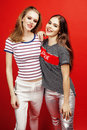 Two best friends teenage girls together having fun, posing emotional on red background, besties happy smiling, lifestyle