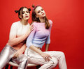 Two best friends teenage girls together having fun, posing emotional on red background, besties happy smiling, lifestyle Royalty Free Stock Photo