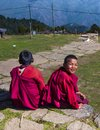 Two cute Bhutanese novice young monks sit on footstep , one turns his head and smiles