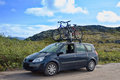 Two bicycles mounted on roof of car against sky Stock Photo