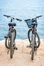 Two bicycles on the pier standing concrete blue water background Royalty Free Stock Images