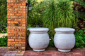 Two big pots next to brick column Royalty Free Stock Images