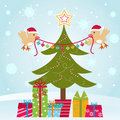 Two birds decorating Christmas tree Stock Image