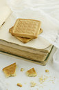 Two biscuits on vintage book pile light background Stock Photo