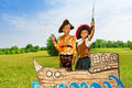 Two black boys in pirates costumes hold swords up kids boy and girl on ship standing close Stock Images