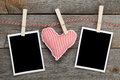 Two blank instant photos and red heart hanging on the clotheslin wooden background Stock Image