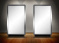 Two blank screens standing on wooden floor with spotlights above Royalty Free Stock Photography