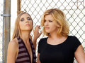 Two blond women against chain link fence Stock Photo