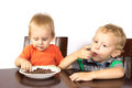 Two blonde brothers eat a race nuts in chocolate Royalty Free Stock Photos