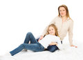 Two blondes mother and daughter hugging sitting on the floor studio photo on white background Royalty Free Stock Images