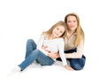 Two blondes mother and daughter hugging sitting on the floor studio photo on white background Stock Photography