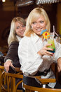 Two blonds at a bar counter with a cocktail Stock Photo